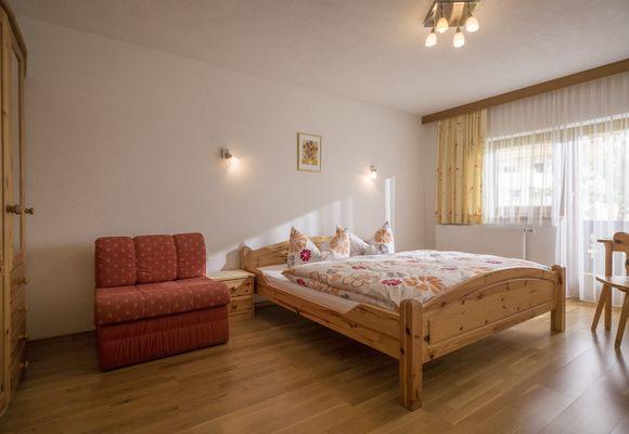Großes Doppelzimmer mit Doppelbett, Couch und großer Fensterfront