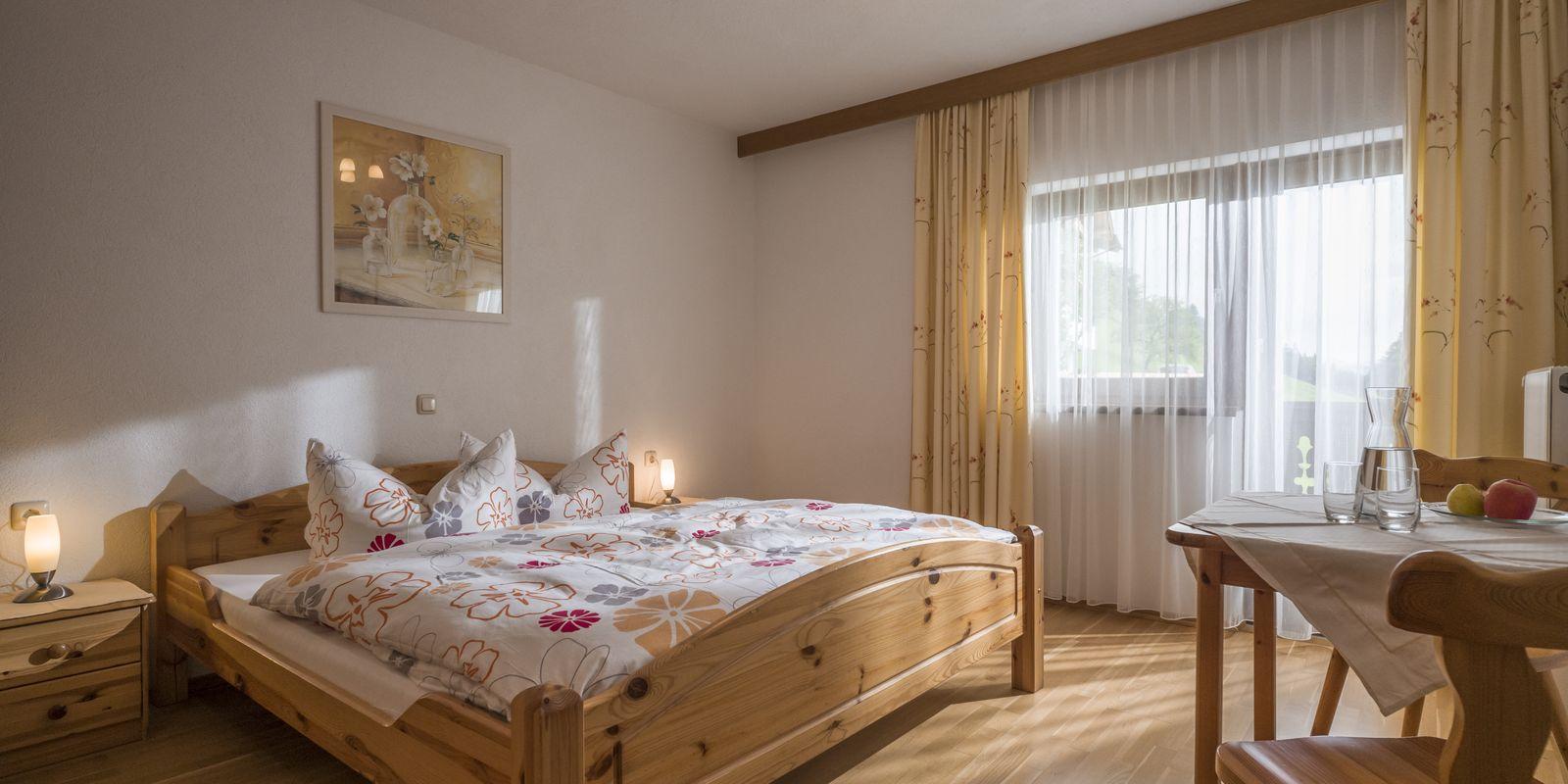 Doppelzimmer mit Blick auf Vollholz-Bett, Sitzgelegenheit und Fenster mit Balkontür