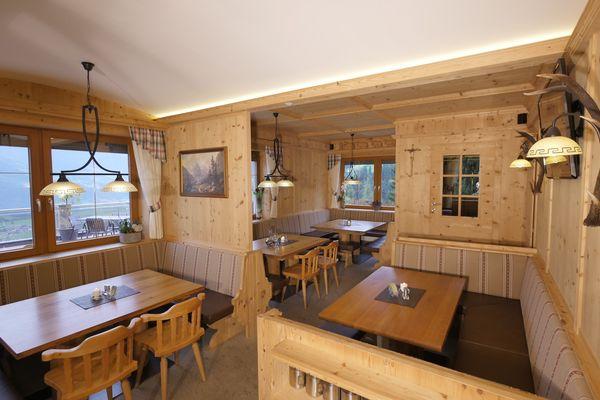 Stube des Gasthof Sonnberg mit Holzvertäfelung, Eckbänken und großen Esstischen