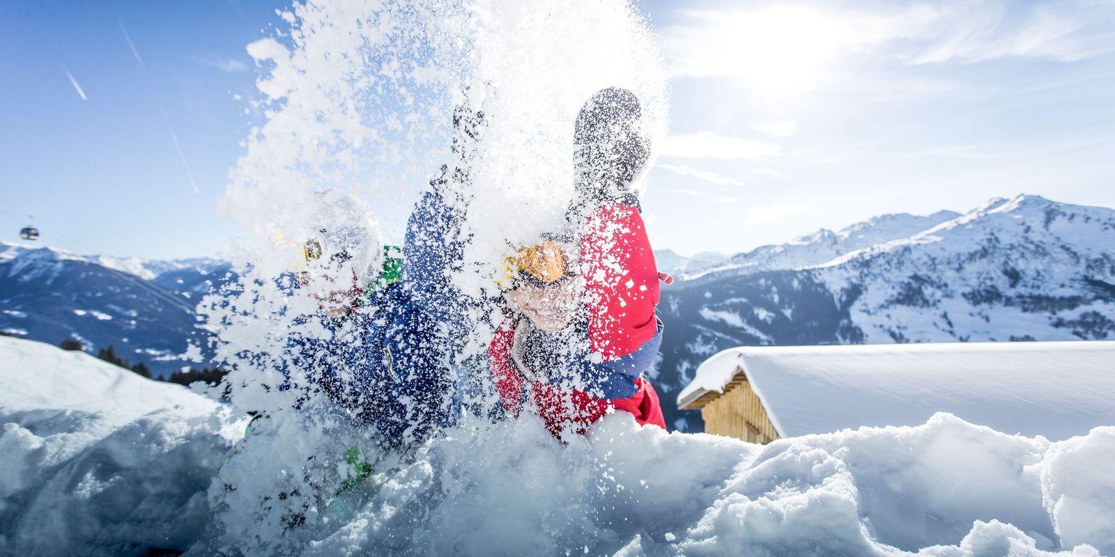Kinder werfen mit Schnee um sich, Sonne und Berglandschaft im Hintergrund