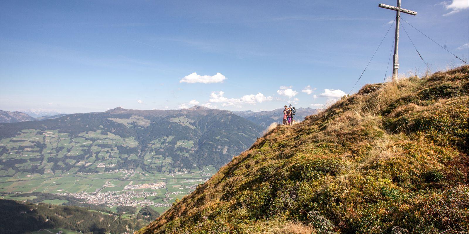 Panoramafoto mit Gipfelkreuz bei einer Familienwanderung