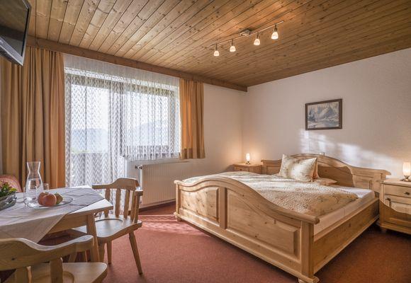 Doppelzimmer im Tiroler Stil mit Sitzgelegenheit, Vollholz-Doppelbett, Fenster und Balkontür