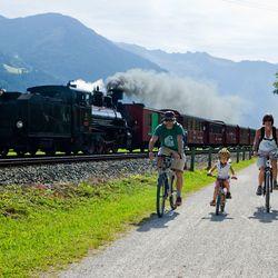 Familie beim Radfahren neben der Dampflok entlang des Zillertaler Radweges