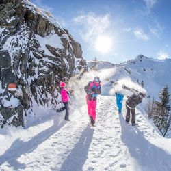 Familie bei einer Schneeballschlacht an einem sonnigen Wintertag während einer Wanderung