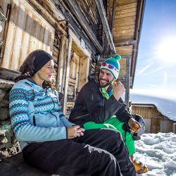 Paar beim Sonne tanken an einer Berghütte im verschneiten Skigebiet